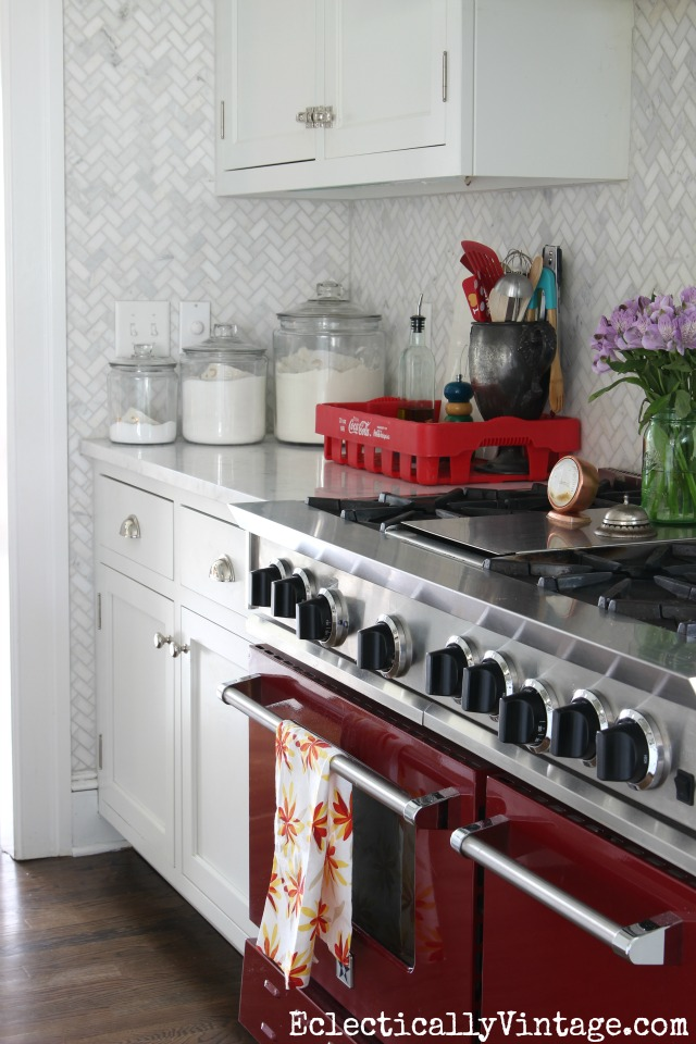 Wow! The red stove is such a fun idea in a white kitchen and love the floor to ceiling carrara marble herringbone backsplash kellyelko.com
