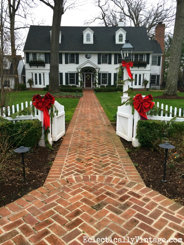 Classic Christmas Homes - love this white beauty decked out in greenery and festive red bows kellyelko.com
