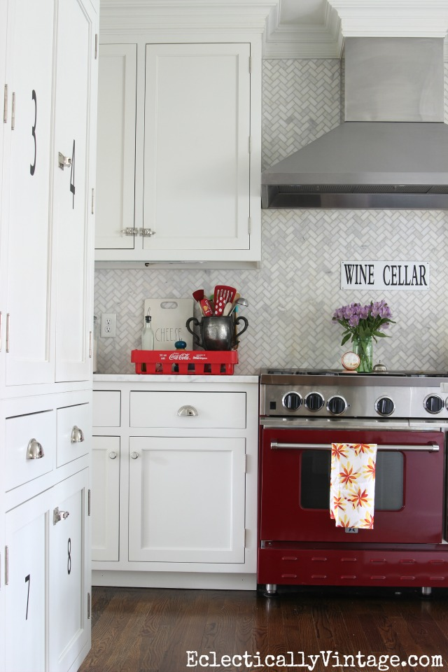 Love this red stove in an all white kitchen and that carrara herringbone backsplash is gorgeous! kellyelko.com