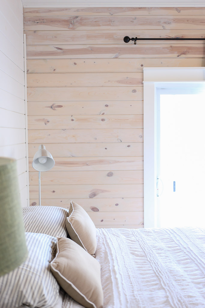 Horizontal knotty pine planked walls mix with painted planks in this cozy bedroom kellyelko.com