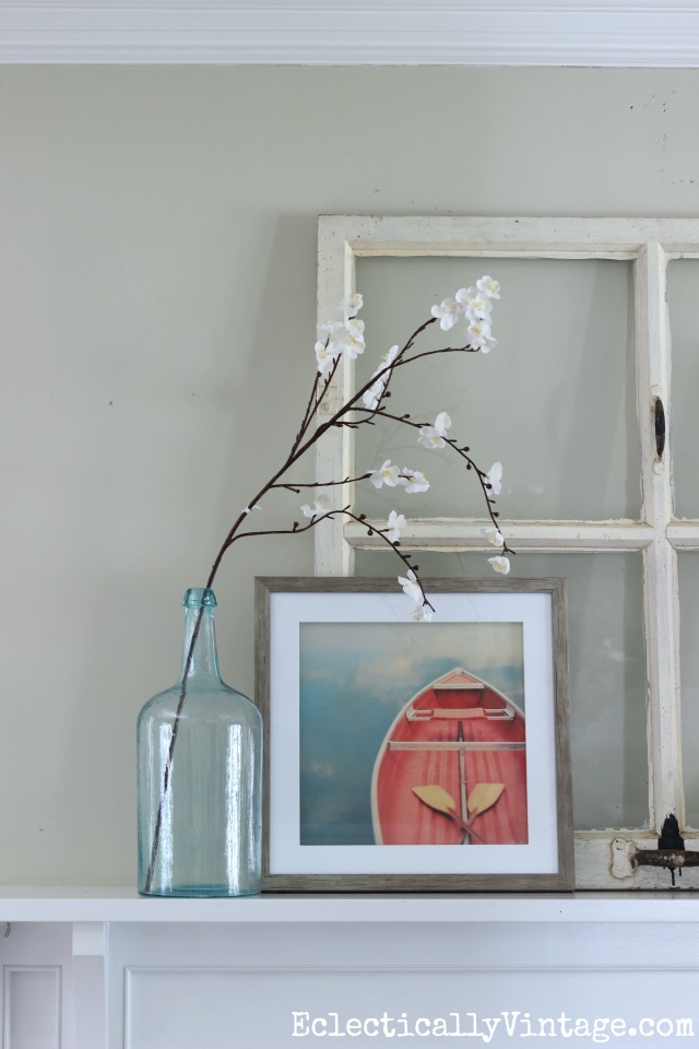 Prop and layer accessories on the mantel for a relaxed look. Love the boat art and the old green bottle holding a single flowering branch kellyelko.com