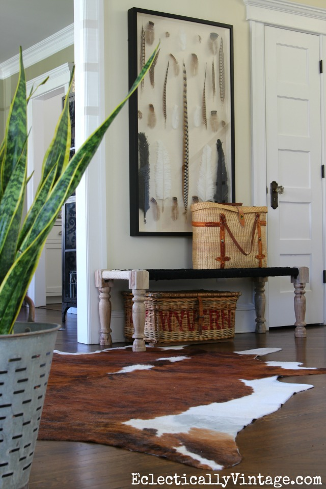 Love the woven bench in this foyer, cowhide rug and the fabulous real feather shadowbox art! kellyelko.com