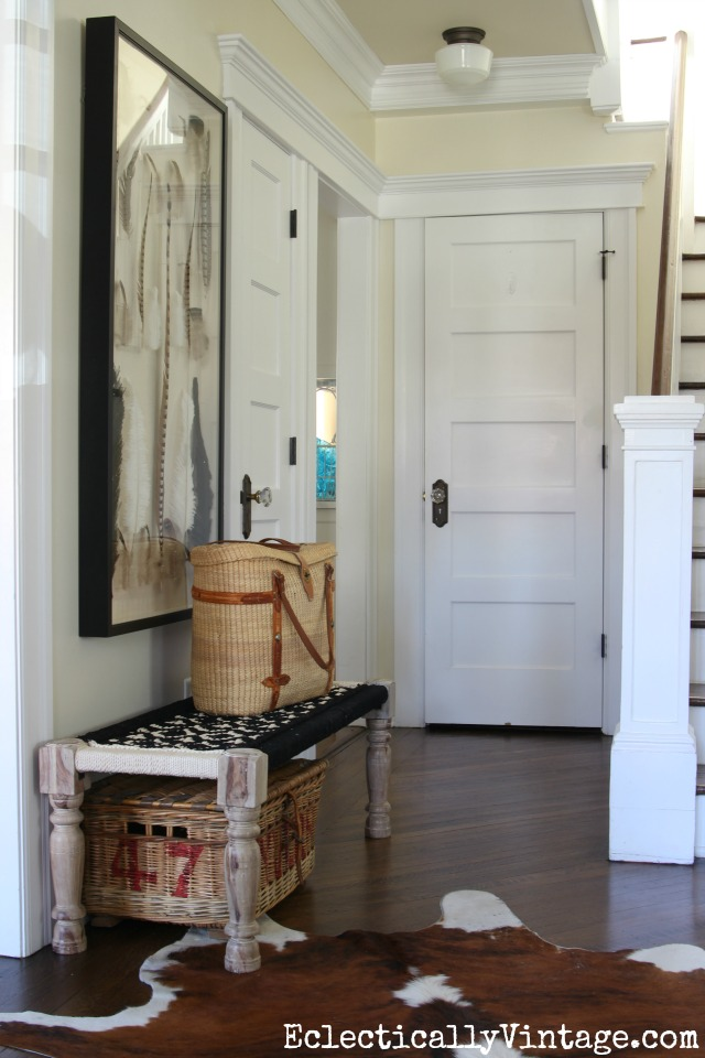 Beautiful foyer with woven bench, cowhide rug and feather art kellyelko.com