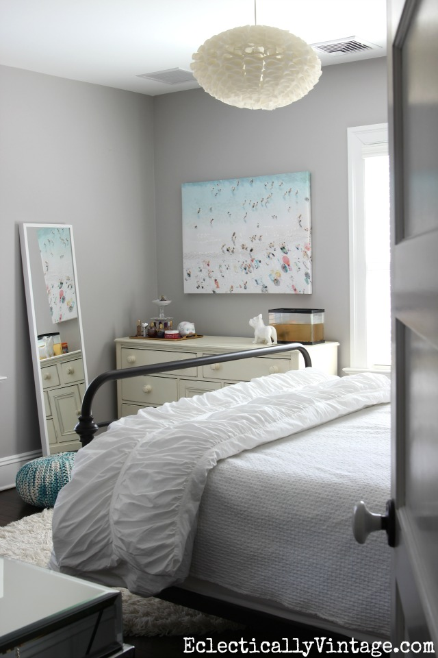 Gorgeous gray bedroom - love the chandelier and the beach art! kellyelko.com