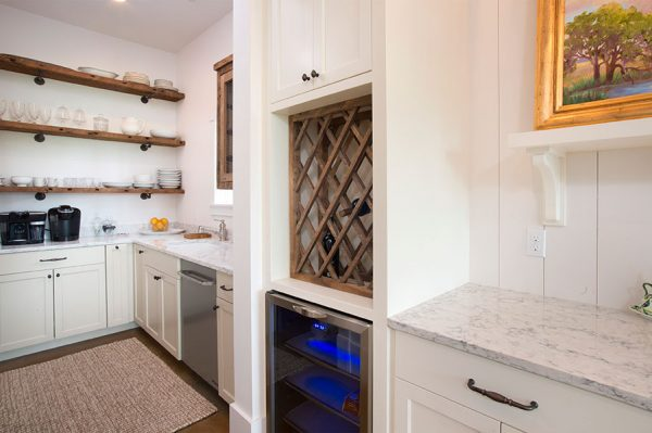 Rustic wood open shelves and wine storage add character to this white kitchen kellyelko.com