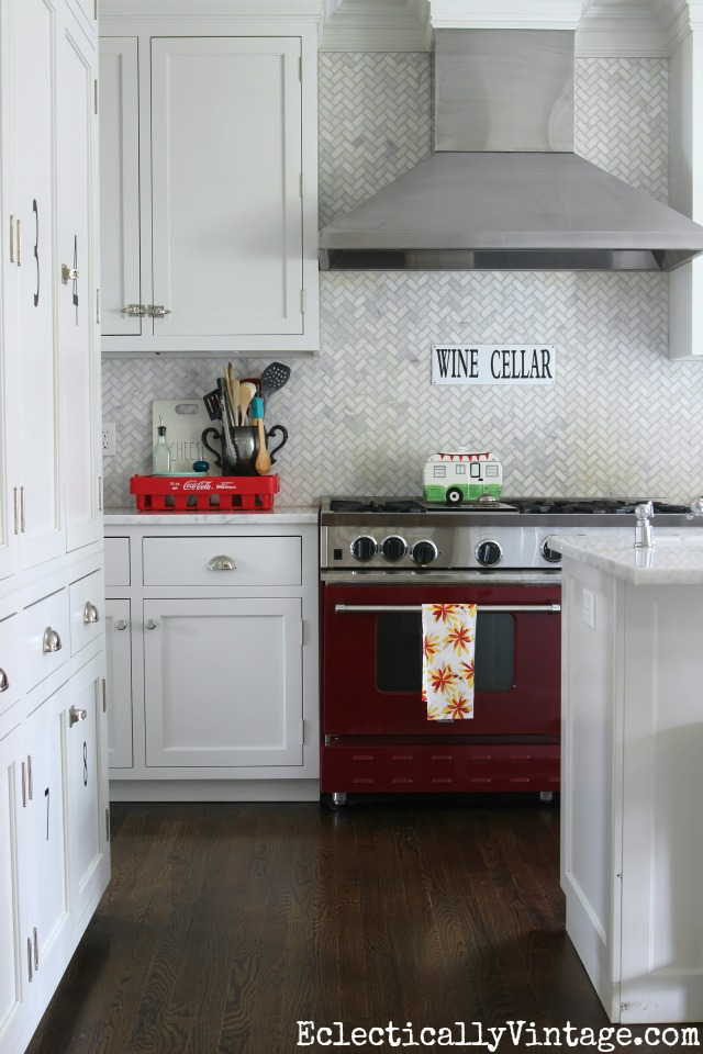 Love this white kitchen and carrara marble herringbone tile - the red stove really pops! kellyelko.com