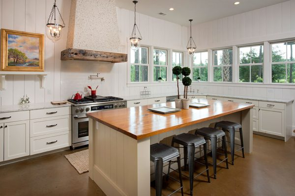 Love this coastal kitchen with tabby shell range hood and vertical plank walls kellyelko.com