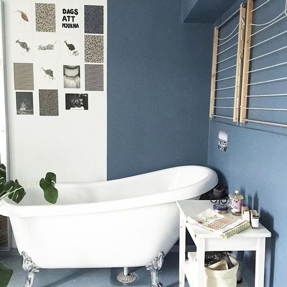 Love the moody blue paint and claw foot tub in this functional bathroom kellyelko.com