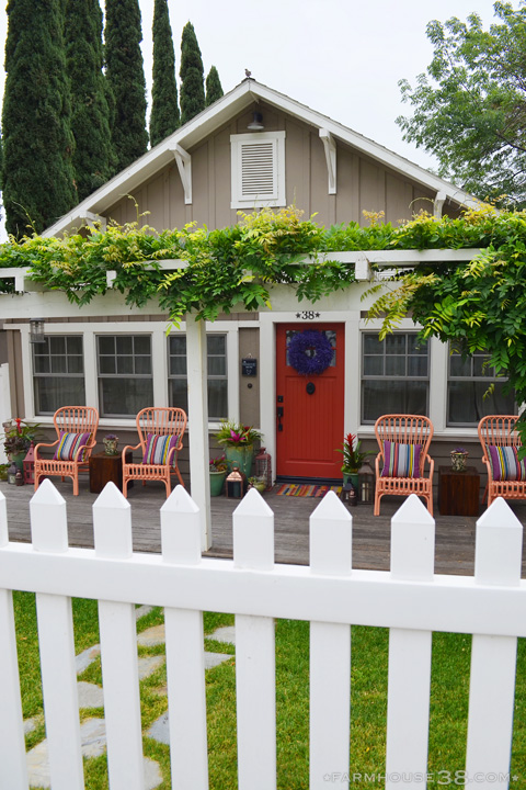 Love this cottage curb appeal with the vine covered pergola, picket fence and red front door kellyelko.com