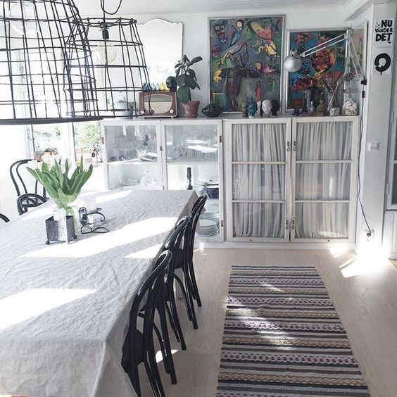 Love the oversized wire chandeliers and glass front cabinets in this minimalistic dining room kellyelko.com