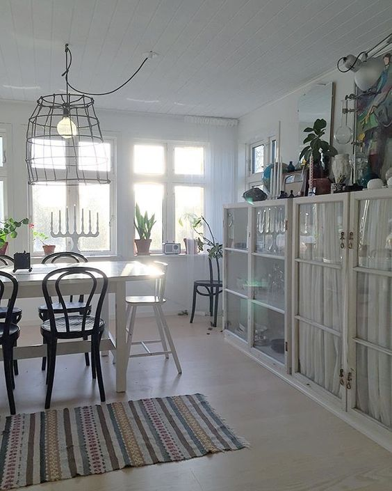 Love the built in glass cabinets in this white dining room with wire chandelier and black bentwood chairs kellyelko.com