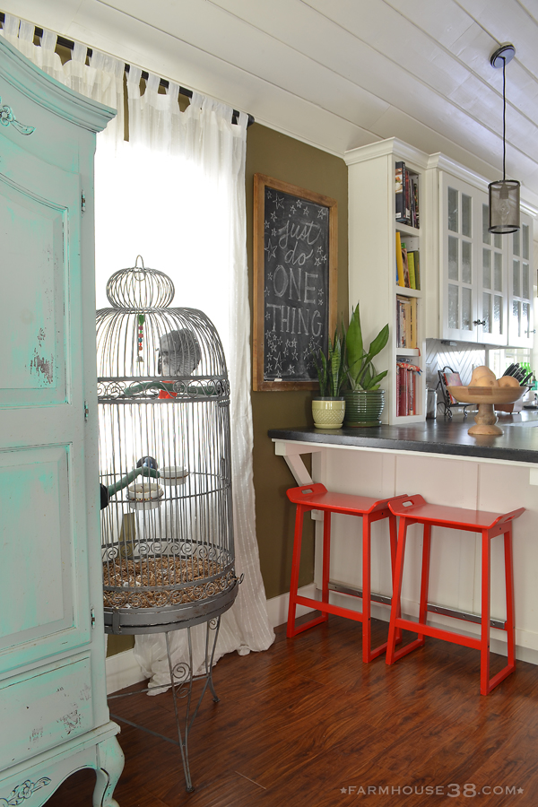 Eclectic and colorful home - love the giant bird cage and red bar stools kellyelko.com