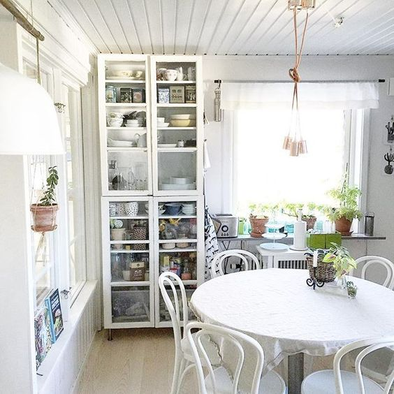 Love this simple kitchen with white bentwood chairs and glass front storage cabinet kellyelko.com