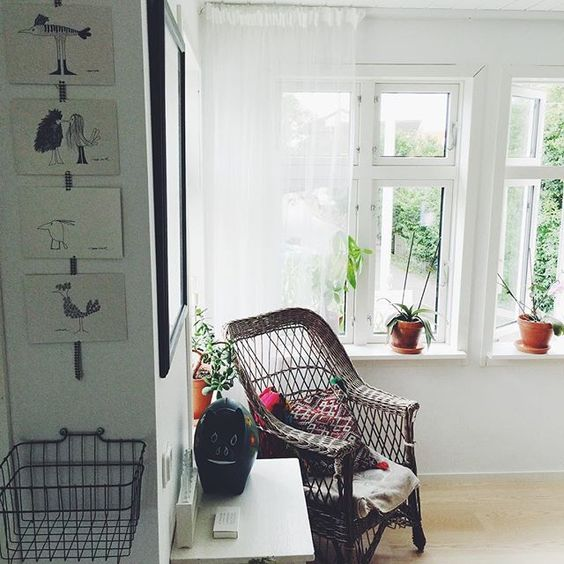 Cozy reading nook - love the wicker chair and all the plants on the windowsill kellyelko.com