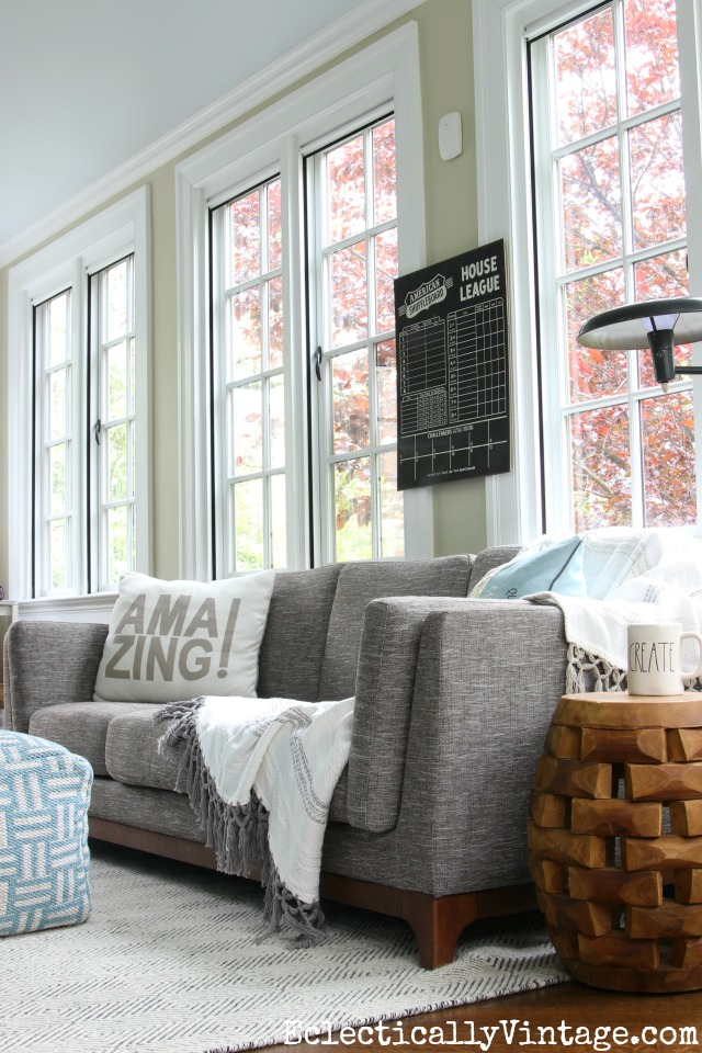 Love the huge windows in this beautiful sunroom with gray sofa and textured black and white rug kellyelko.com