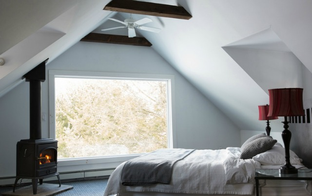 Love this cozy attic bedroom with exposed beams and wood burning stove kellyelko.com