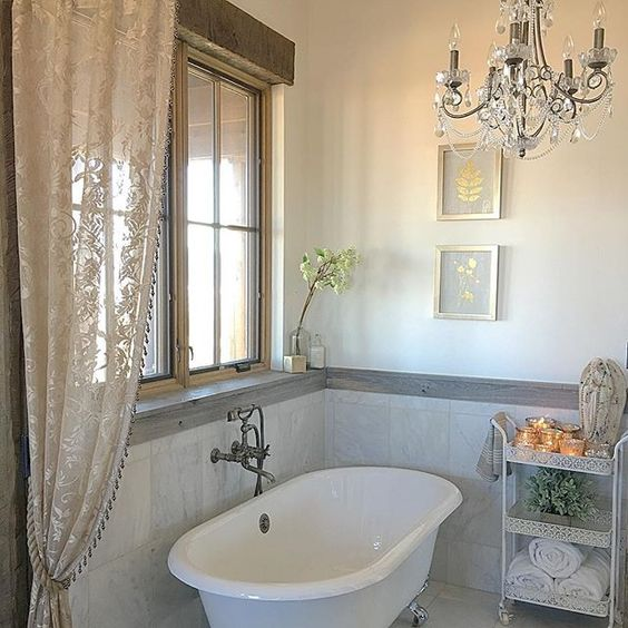Love the claw foot tub and crystal chandelier in this farmhouse bathroom kellyelko.com