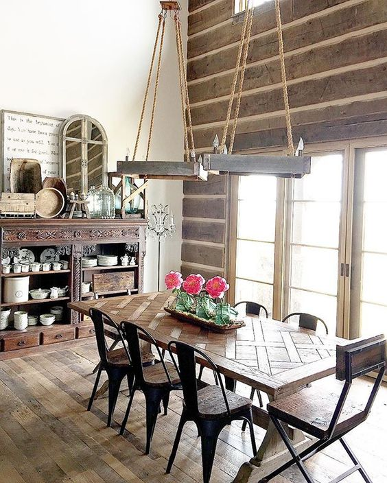 Love this rustic dining room - the rope chandeliers and farmhouse table paired with metal chairs are beautiful kellyelko.com