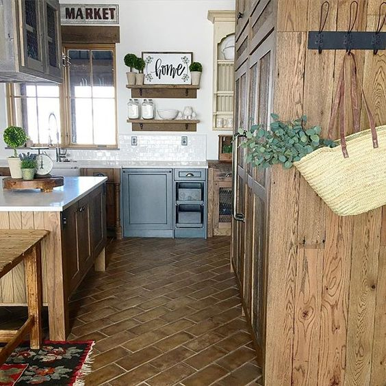 Love the rustic tile floor and blue lower cabinets in this farmhouse kitchen kellyelko.com