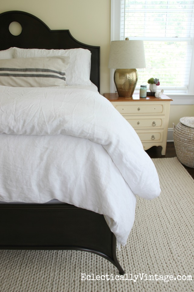 Serene neutral master bedroom with iron bed, neutral vintage linen duvet and bedding and hammered brass lamp kellyelko.com