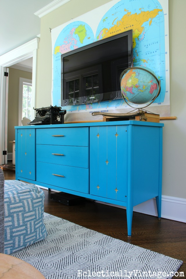 Love this blue painted mid century furniture - the perfect media cabinet and the vintage map is such a fun piece of wall art behind the tv kellyelko.com