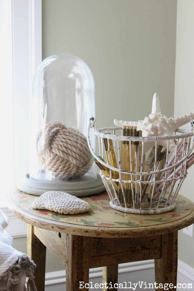 Love this coastal decor - the rope monkey ball under a cloche and a metal basket filled with old folding rulers and a starfish kellyelko.com