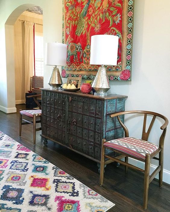 Eclectic mix of furniture in this colorful foyer - love the colorful tapestry kellyelko.com