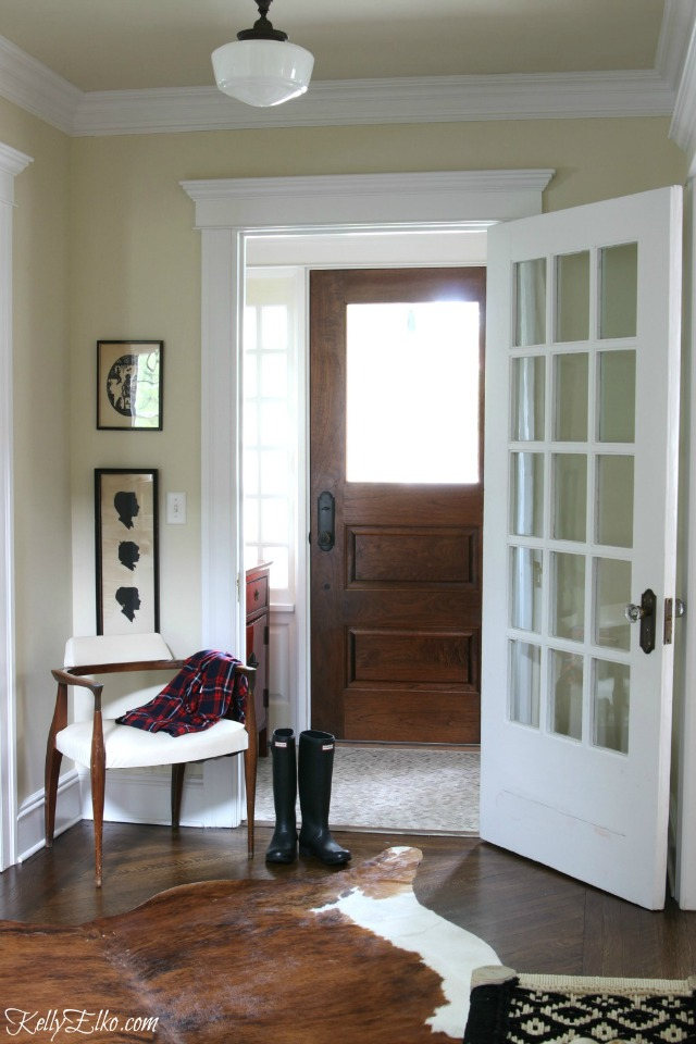 Love this neutral foyer with cowhide rug and schoolhouse light kellyelko.com