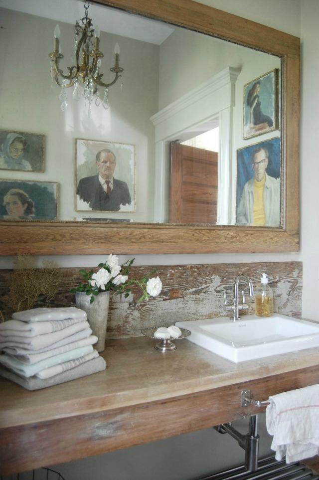 Rustic wood bathroom counter with a fun portrait gallery wall kellyelko.com